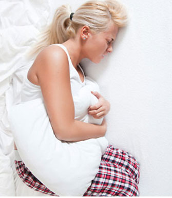 Kobieta leżąca na łóżku i trzymająca poduszkę na bolącym brzuchu