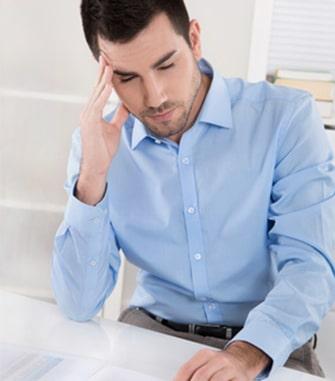Mężczyzna dotyka ręką bolącej głowy