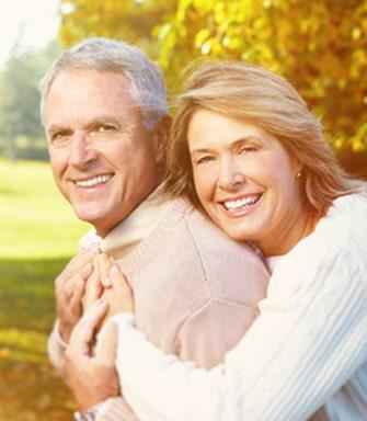 Kobieta i mężczyzna w dojrzałym wieku, obejmują się i uśmiechają