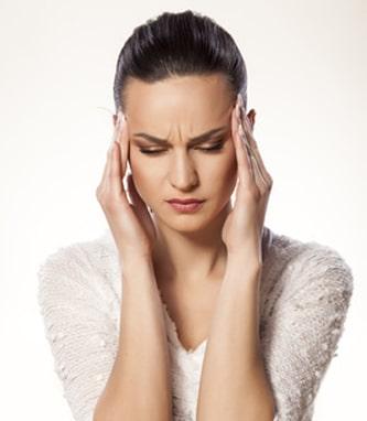 Kobieta trzymająca ręce na skroniach cierpiąca na ból głowy